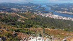 Aerial view of the CerLove giant wooden swing in Vila Nova de Cerveira, Portugal. The swing of the valley of Minho is next to the viewpoint of  of Cervo. People on swings admire the view.
