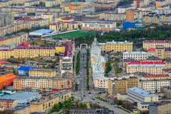 Aerial view of the city of Magadan. Portovaya street and the arch with the text in Russian