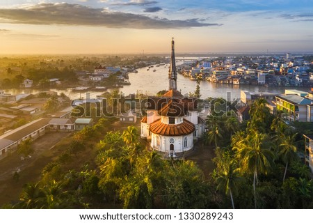 Aerial view of the famous Cai Be church in the Mekong Delta, Roman architectural style. In front is Cai Be floating market, Tien Giang, Vietnam