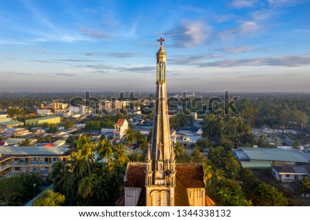 Aerial view of the famous Cai Be church in the Mekong Delta, Roman architectural style. In front is Cai Be floating market on Tien Giang river, Vietnam. Bell tower with the statue of Blessed Mother