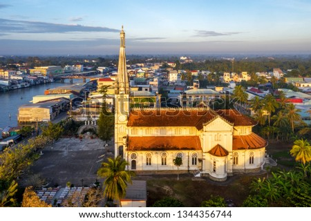 Aerial view of the famous Cai Be church in the Mekong Delta, Roman architectural style. In front is Cai Be floating market on Tien Giang river, Vietnam