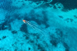 Aerial view of the fishing boat in clear blue water at sunset in summer. Top view from drone of yacht, sandy beach in Indian ocean. Travel in Zanzibar, Africa. Tropical landscape with motorboat, sea