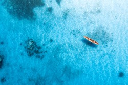Aerial view of the fishing boat in transparent blue water at sunny day in summer. Top view from above of boat, sandy beach. Indian ocean in Zanzibar, Africa. Landscape with canoe and clear sea. Travel