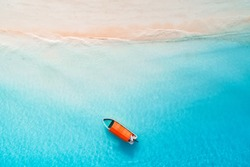 Aerial view of the fishing boats in clear blue water at sunny day in summer. Top view from drone of boat, sandy beach. Indian ocean in Zanzibar, Africa. Landscape with sailboats, clear sea. Seascape