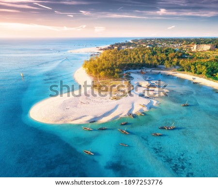 Aerial view of the fishing boats on tropical sea coast with sandy beach at sunset. Summer travel in Zanzibar, Africa. Top view of boats, yachts, green palm trees, clear blue water, colorful sky