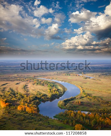 Aerial view of the forest under clouds during the autumn.