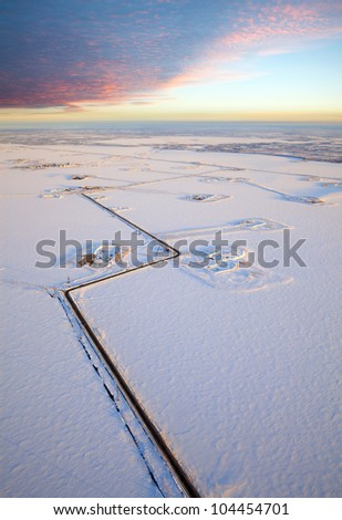 Aerial view of the frozen lake on which are made petroleum production. Roads were run directly through the lake. High clouds bright are lighted by morning sun.