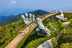 Aerial view of the Golden Bridge is lifted by two giant hands in the tourist resort on Ba Na Hill in Da Nang, Vietnam. Ba Na mountain resort is a favorite destination for tourists
