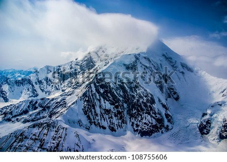 Aerial View of the Great Mount McKinley (Denali) Peak in the Alaskan Wilderness, Denali National Park, AK.  Snow and clouds forming/blowing off the peak.  A Beautiful Snowscape of Rock, Snow, and Ice.