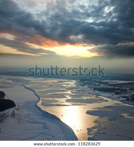 Aerial view of the great river with floating ice floes during sundown. Drifting of ice. Driving of ice. Ice floe.