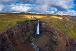 Aerial view of the Hengifoss waterfall in East Iceland. Hengifoss is the third highest waterfall in Iceland and is surrounded by basaltic strata with red layers of clay between the basaltic layers.