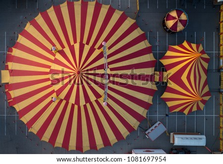 Aerial view of the large circus tent, red-yellow striped, the main, big tent and two smaller ones in colorful light.