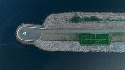 Aerial view of the Lighthouse on the fairway in the Gulf of Finland, navigation is open, summer time. Concrete slabs on the coastline. Breakwaters at the entrance to the port