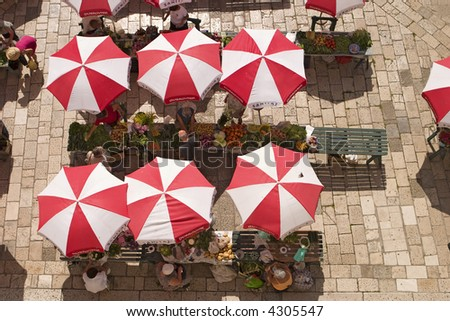 Aerial view of the local farmer's market (Sanitat) in Dubrovnik. The produce is all displayed on tables under the red and white umbrellas.