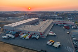 Aerial view of the logistics park with warehouse, loading hub and many semi trucks with cargo trailers standing at the ramps for load/unload goods at sunset