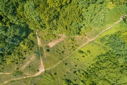 Aerial view of the mountain dirt road and forest in summer. Skyview abstract landscape. Carpathian mountains. Ukraine