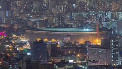 Aerial view of the National stadium in the Peruvian capital Lima from San Cristobal hill night timelapse. Landscape of slum urban area and historic buildings in South America. Peru