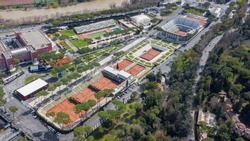 Aerial view of the red clay tennis courts of the Foro Italico, a sports facility in Rome hosting the Italian international tournament. In the background the main stadium.