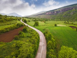 Aerial view of the road in mountain valley. Aerial drone view of asphalt roadway and  meadows with green grass in spring.Nature outdoors travel destination, Stara Planina (Balkan mountain), Serbia.