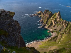 Aerial view of the rough coast of the Norwegian Sea in the north of Andøya island, Vesterålen, Norway with beautiful turquoise colored rock beach, mountains and rugged cliffs on sunny summer day.