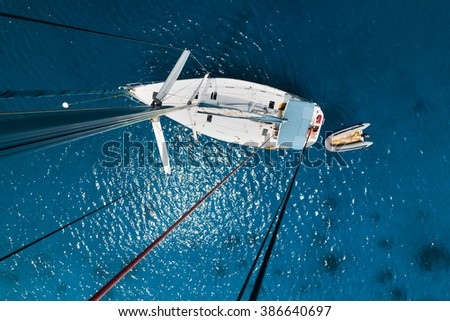 Aerial view of the sailboat anchored in the tropical calm sea