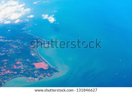 Aerial view of the shore covered by fields areas with blue sea