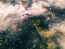 Aerial view of the small settlement surrounded by mountains. Drone flight through the clouds and mist. Peaks of the mountains. Carpathians