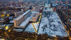 Aerial view of the snow-covered rooftops of the winter city in Lombardy. View of houses and streets through the clouds. Sunset view over the clouds from a height. Drone. Winter. Milan Italy 2021