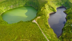 Aerial view of the stunning and sunlit  black and green lake (Lagoa Negra and Lagoa Comprida) on Flores island at the Portuguese achipelago of the Azores in the middle of the Atlantic Ocean