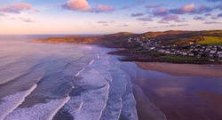 Aerial view of the town of Woolacombe and it's beach at dawn, waves breaking on a beach, the headland of Morte Point bathed in sunlight and hazy with spray kicked up by the breaking waves.