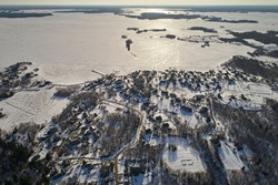 Aerial view of the village and the frozen lake in the winter afternoon. Abstract landscape of the northern nature of Finland with drone.