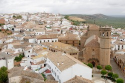 Aerial view of the village of Baños de la Encina in Jaén, with a church, a square with trees white houses and a windmill in the background.
