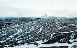 Aerial view of the volcanic desert on Iceland, in the background a glacier, black rock, filming location Interstellar