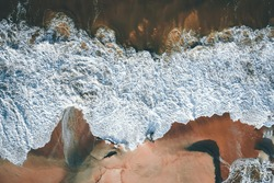 Aerial view of the waves reaching the beach shore