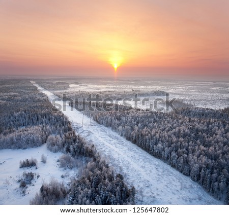 Aerial view of the winter forest and electricity line on background of sundown.