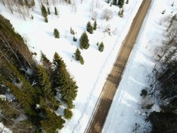 Aerial view of the winter landscape in Russia. Snowy spruce forest, pine trees. Aerial view on road in winter time, road surrounded with forest trees, car driving in winter time. Captured with a drone