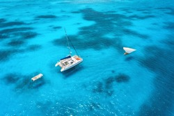Aerial view of the yacht and sailboat in clear blue sea at sunset in summer. Top view of fishing boat, yachts, sandy beach, transparent water in Zanzibar. Travel. Tropical seascape. View from above
