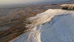 Aerial view of thermal pools hot springs tavertine terraces of Pamukkale natural park, white cotton castle, snow white mountains with carbonate mineral milky pools, Turkey