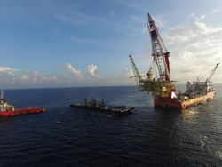 Aerial view of topside installation by heavy lift vessel captured by drone