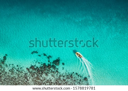 Aerial view of tourist boat on surface of amazing tropical turquoise ocean coastline with coral reef. Aqua Menthe trendy color of the new year 2020. Stock photo ©