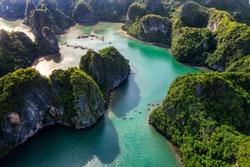 Aerial view of tourists on the boat in Vung Vieng floating fishing village and rock island, Halong Bay, Vietnam, Southeast Asia. UNESCO World Heritage Site. Junk boat cruise to Ha Long Bay.
