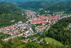 Aerial view of town of Bad Urach, Germany, Europe. Panorama of small city in Swabian Alps, inhabited locality in Baden-Wurttemberg. Terrain with forest and houses, summer landscape taken from above.