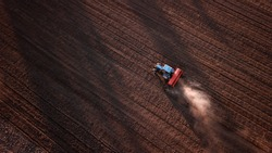 aerial view of tractor , combine cultivating field. drone shot. picture with space for text. Farmland from above