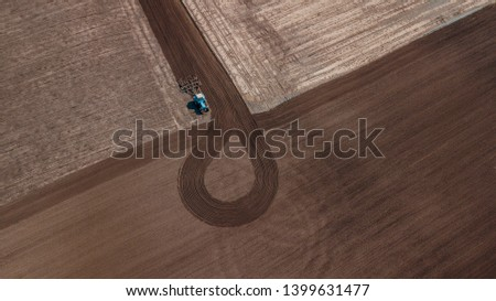 aerial view of tractor , combine cultivating field. drone shot. picture with space for text. Farmland from above #1399631477