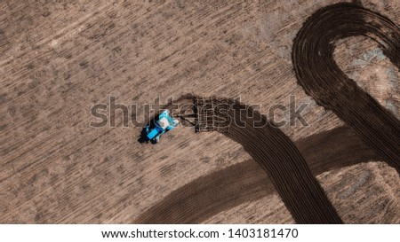 aerial view of tractor , combine cultivating field. drone shot. picture with space for text. Farmland from above #1403181470