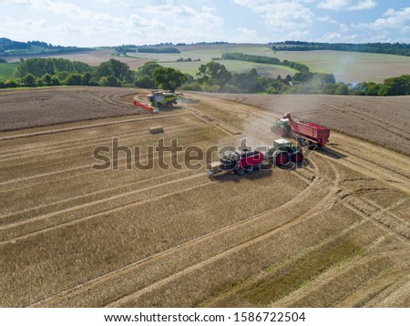Aerial view of tractor pulling baler making straw bales in harvested wheat field and combine harvester harvesting