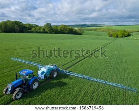 Aerial view of tractor spraying crop in green farm fields with pesticide stock photo
