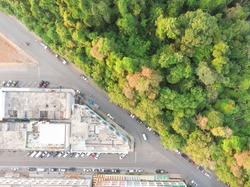 Aerial view of traffic road and building beside a natural public park  in middle of city.Scenic view cityscape building and tree from drone