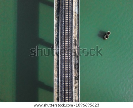 Aerial view of train railway over the river in Thailand. Top view of railroad from drone.