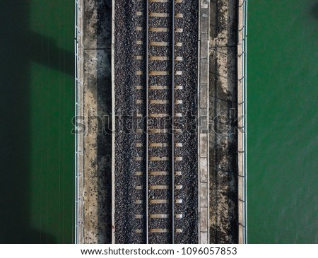 Aerial view of train railway over the river. Top view of railroad from drone.